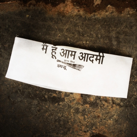 AAP's Gandhi topi - printed text reads 'I Am The Common Man' followed by the election symbol of the broom